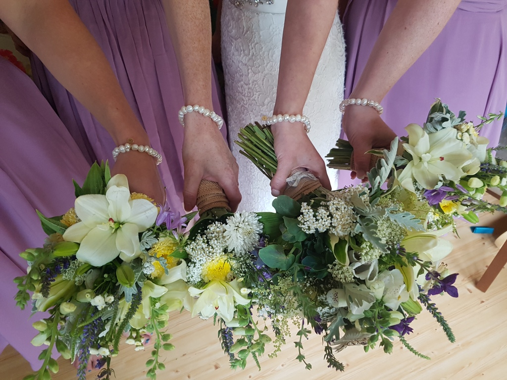 fours hands holding white bouquets and wearing pearl bracelets